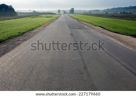 autumn landscape empty asphalt road among meadows leads to the horizon in the early misty morning - stock photo