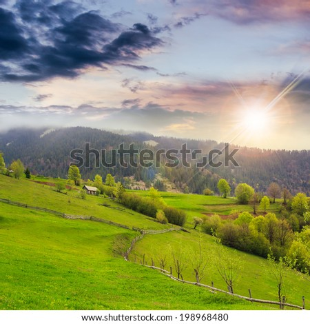 autumn landscape. fence near the meadow path on the hillside. forest in fog on the mountain at sunset