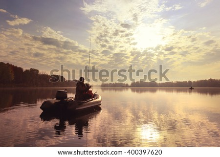 autumn landscape fisherman in an inflatable boat in the early morning on the river - stock photo