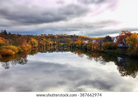 Autumn landscape in a rural area, near a crystalline river in Germany. Cloudy sky, multicolored plants and trees. Vineyards and rustic agriculture.(relaxation, peace and silence)