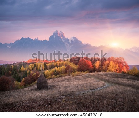 Autumn landscape in mountains. Deciduous forest in hills. Stack dry hay in meadow. Rural view from footpath. Beautiful sunset. Art processing of photos. Low contrast, color toning, soft focus effect