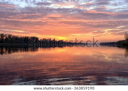 autumn landscape magnificent sunset over the river and reflected clouds in a mirror surface  - stock photo