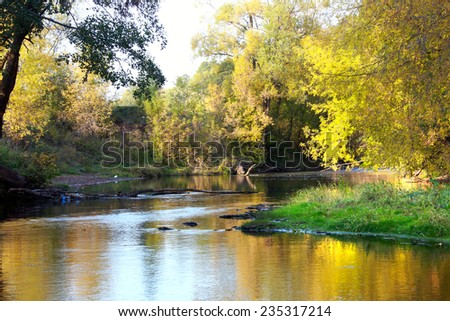 autumn landscape mirror-like surface of the river and the yellowing trees on the shore on a sunny day - stock photo