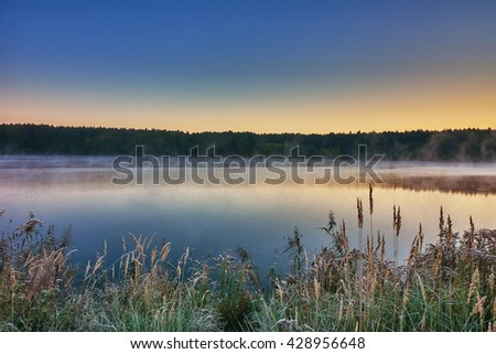 Autumn landscape - morning twilight over the lake. Fog over the water, the grass covered with frost. - stock photo