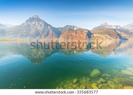 Autumn landscape of a mountain lake. In the clear water visible stones on the bottom. Fallen leaves on the water surface.