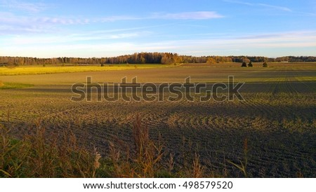 Autumn landscape of local farm fields in afternoon sun with blue sky, located in Southern Finland, Europe