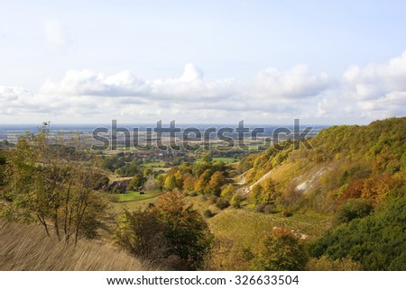 Autumn landscape of the distant Vale of York viewed from the scenic wooded valley of Thixendale in the Yorkshire wolds in October - stock photo