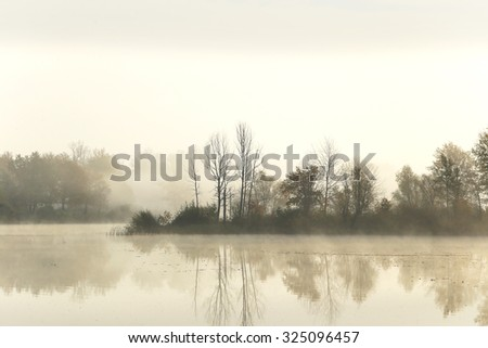 autumn landscape on the river early in the morning, the reflection of the sky in the mirrored surface