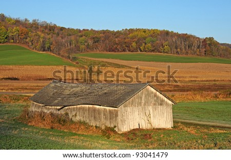 Autumn landscape scene: old shed in field with ripened corn field and colorful trees on hill in background - stock photo