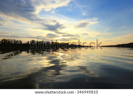 autumn landscape sunset over the river and reflected clouds in a mirror surface  - stock photo