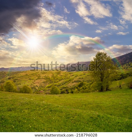 autumn landscape. village near the meadow path on the hillside. forest in fog on the mountain with rainbow at sunset - stock photo