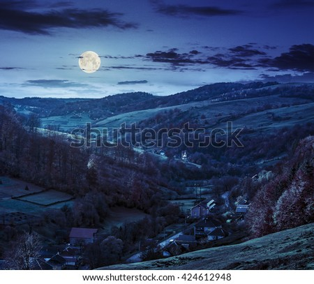 autumn landscape. village on the hillside. forest on the mountain covered with red and yellow leaves at night in full moon light - stock photo