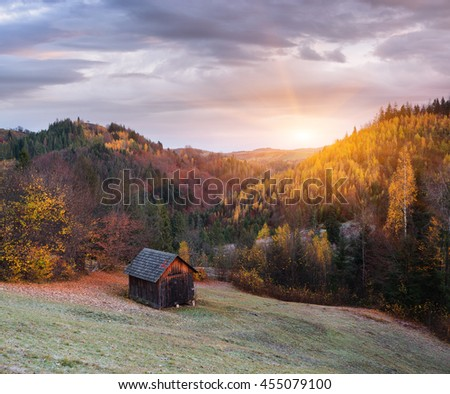 Autumn Landscape with a wooden house. Colorful forest on the slopes of the mountains. Beautiful light and sun rays - stock photo