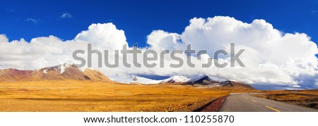 autumn landscape with grassland and road - stock photo