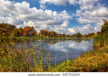 Autumn landscape with lake and blue sky