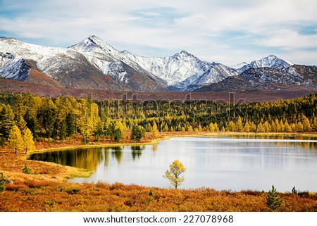 Autumn landscape with lake and snow mountains  - stock photo