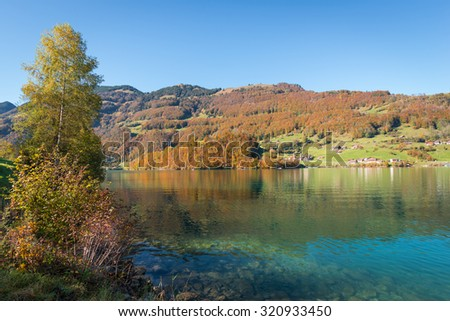 Autumn landscape with reflection in the water. Gorgeous sunny day.