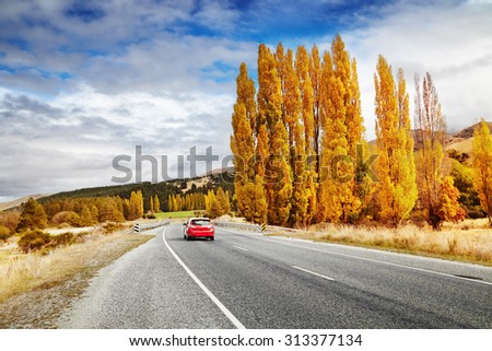 Autumn landscape with road and red car, New Zealand - stock photo