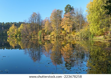 Autumn landscape with trees reflecting in a lake with calm surface, Russia