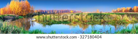 autumn landscape with yellow trees on river coast panoramic - stock photo