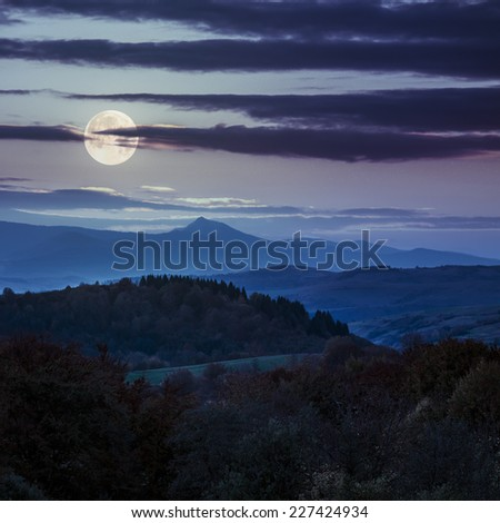 autumn landscape. yellow trees near green meadow in foggy mountains at night in full moon light