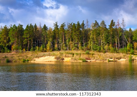 Autumn lanscape with pine forest and lake