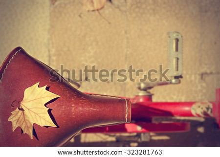 Autumn leaf over the saddle of an old bike. Vintage style. Concept arrival autumn. Horizontal image.