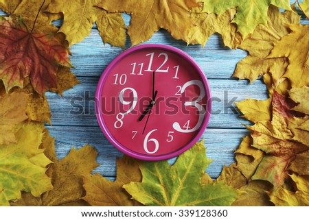 Autumn leaf with o'clock on a blue wooden table - stock photo