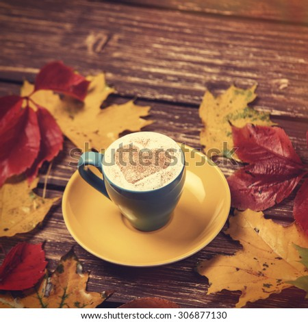 Autumn leafs and coffee cup on wooden table.