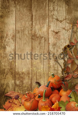 Autumn leaves and pumpkins on a wooden background - stock photo