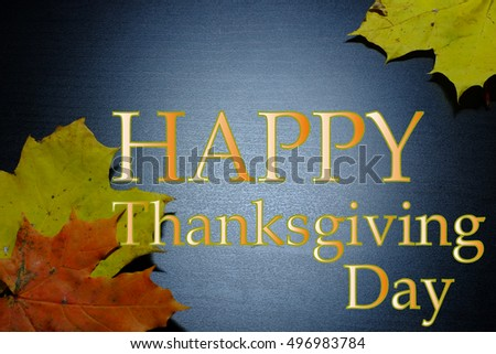 Autumn leaves on a dark background. With the caption Happy Thanksgiving Day.