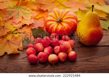 Autumn leaves on wooden table. Fruits and vegetables, apple, pear, pumpkin