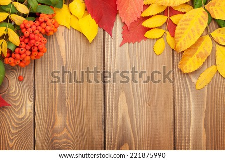Autumn leaves over wood background with copy space - stock photo