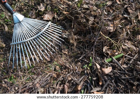 Autumn leaves raking up pile in spring garden on countryside  Cleaning lawn with metal in spring to prepare plot for planting flowers and vegetables, text message copyspace for magazines, blogs - stock photo