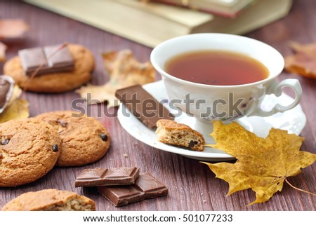 Autumn lifestyle with hot tea, sweets and yellow leaves on the wooden background
