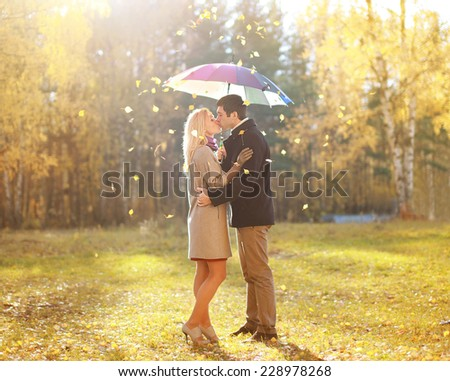 Autumn, love, relationship and people concept - happy kissing couple in love outdoors in autumn park, leafs fall  - stock photo