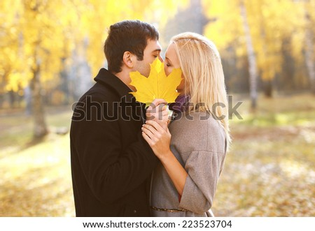 Autumn, love, relationships and people concept - pretty couple kissing in autumn park - stock photo