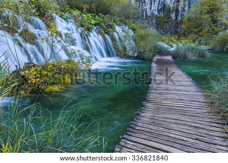 Autumn majestic view on turquoise water and falls with wooden path road in the Plitvice Lakes National Park. Croatia.