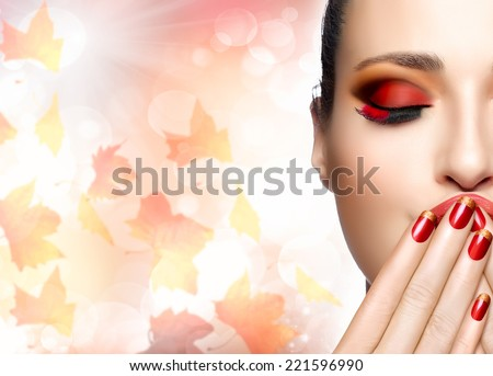 Autumn makeup and nail art trend. Fall beauty fashion girl. Professional makeup and manicure. Closeup portrait of half face on autumnal background with falling leaves - stock photo