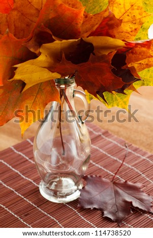 Autumn maple leaves bouquet in a glass bottle