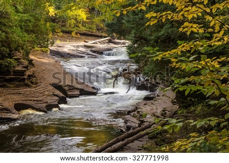 Autumn Michigan Waterfall. Waterfall in the Porcupine Mountains of Michigan's Upper Peninsula framed by autumn foliage. - stock photo