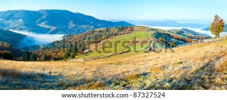 Autumn misty morning plateau with stack of hay and country dirty road (Mighgirya village outskirts, Carpathian Mt's, Ukraine). - stock photo