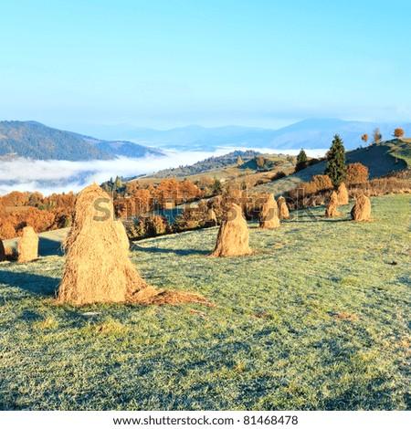 Autumn misty morning plateau with stack of hay (Mighgirya village outskirts, Carpathian Mt's, Ukraine). - stock photo