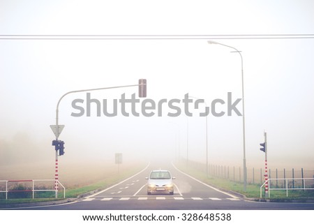 Autumn misty road with cars