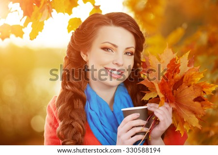 Autumn model, bright make up. woman on background fall landscape leaves of trees. Girl Model on autumn season. Fashion people. hot coffee in her hands