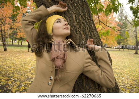 Autumn mood. Young attractive cheerful woman posing at park - stock photo