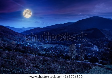 autumn moon landscape. village on the hillside. forest on the mountain covered with red and yellow leaves. - stock photo
