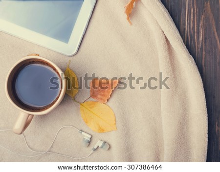 Autumn morning. Cup of coffee, tablet, earphones and warm blanket, top view. Toned photo. - stock photo