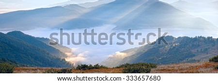 Autumn morning mountain view with sunbeam and haze. - stock photo