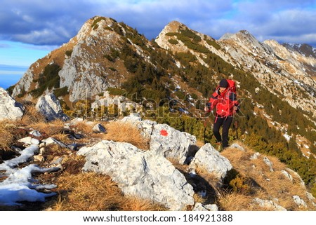 Autumn mountain and backpacker on sunny trail - stock photo